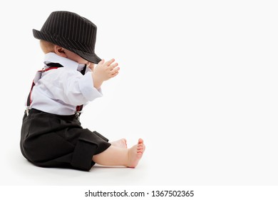 Cute baby boy in black hat is siting in the studio on a white background.