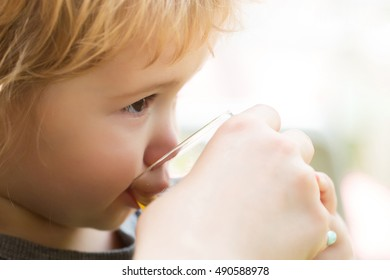 Cute baby boy blond kid with brown eyes drinks juice from glass on white background