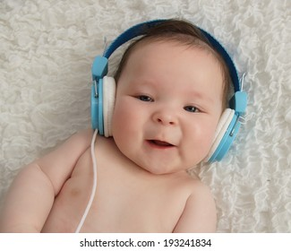 Cute baby boy with blue headphones on ears