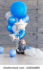 Cute baby boy celebrating birth day with air balloons. Scene of kid with presents and blue balloons.