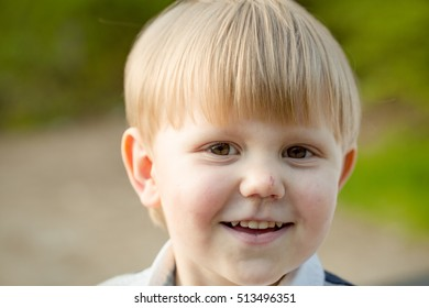 Cute baby boy child or kid smiling with blond hair with funny face outdoors on summer day on natural background