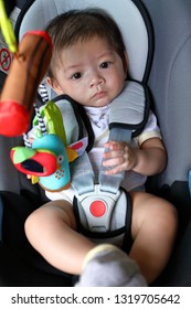 cute baby boy child sitting in car seat with safety belt locked protection