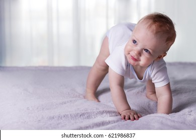 Cute baby boy doing first steps. Lovely infant kid begining to toddle.
