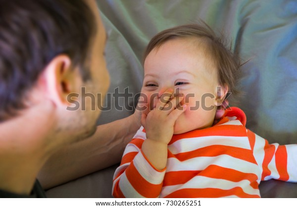 Cute baby boy with Down syndrome playing with dad on the bed in home bedroom