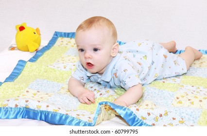 Cute baby boy, dressed in blue, lays on tummy on handmade quilt with mouth open