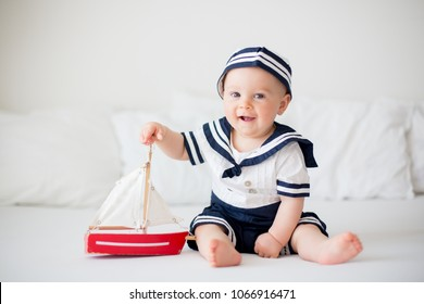 Cute baby boy, dressed in sailor clothes, playing with wooden boat