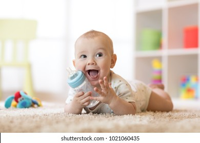 Cute baby boy drinking from bottle. Kid lying on carpet in nursery at home. Smiling child is 7 months old.