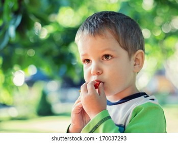 cute baby boy eating cherry outdoor