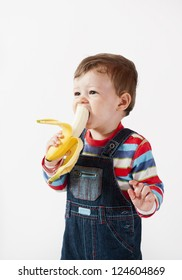 Cute baby boy eats banana.