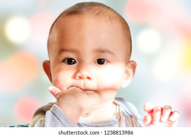 Cute baby boy with finger in his mouth with shallow depth of field