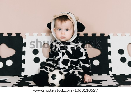 eea733cf61 cute baby boy with football ball sits on black and white clothing, sports,  active