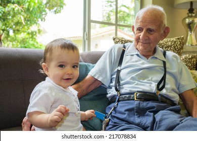 Cute baby boy with great grandfather in a home setting.