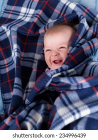Cute baby boy hiding in soft plaid and laughing