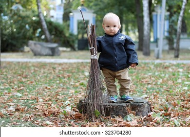Cute baby boy holding a broom in the city park