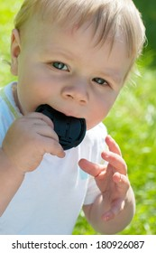 Cute baby boy holding lens cover on his mouth, outdoor