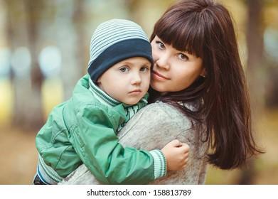 cute baby boy hug his lovely mom in autumn park