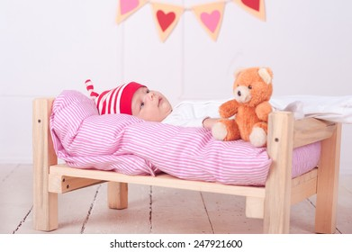 Cute baby boy lying in bed with teddy bear and valentines heart at background. Bed time. Resting.