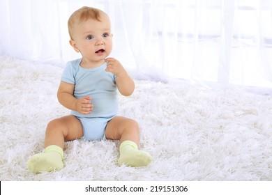 Cute baby boy on carpet in room