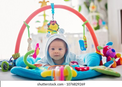 Cute baby boy on colorful gym, playing with hanging toys at home, baby activity and play center for early infant development. Kids playing at home