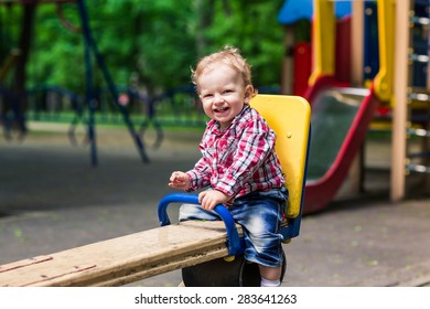 Cute baby boy on a seesaw swing at the playground