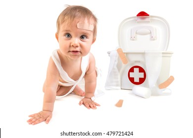 Cute baby boy playing with bandages in a first aid kit box.