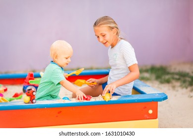 Cute baby boy playing with his sister with toys in the sandbox outdoor