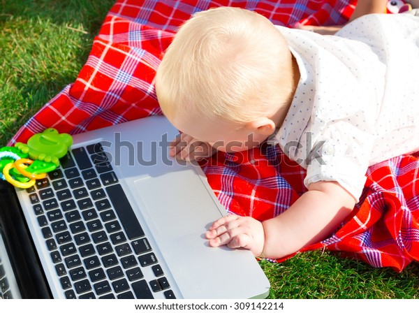 Cute baby boy playing with laptop and toys outdoors on green grass.Wondered baby looks at notebook screen.little boy playing outdoors with a laptop.baby boys face getting into on a laptop computer