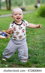 Cute baby boy playing and laughing in the park. Summer is around a lot of greenery  interesting things for crumbs. Kid 1 year