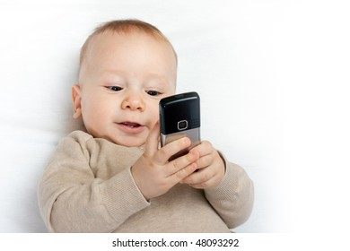 cute baby boy playing with mobile phone on white - closeup