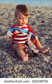 The cute baby boy playing on the beach. Little boy sitting on the sand. Sea and seashore as background.