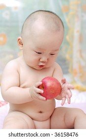 cute baby boy  playing  red apple