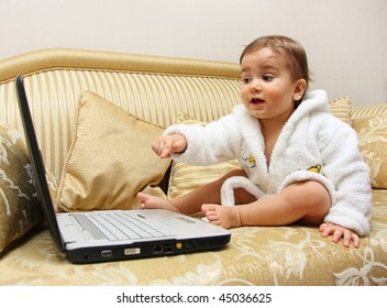 Cute baby boy pointing with the finger on laptop