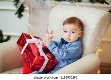 Cute baby boy with the present box under the Christmas tree. Christmas concept.