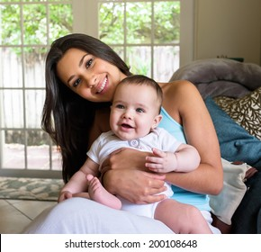 Cute baby boy with pretty young woman in a home setting.