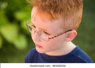 Cute baby boy with red hair in blue t-shirt and eyeglasses poses on summer day on natural background