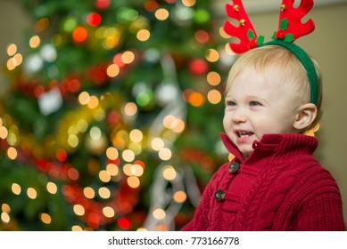 Cute baby boy in a red knit sweater wearing felt reindeer antlers laughing in front of a christmas tree in a living room.