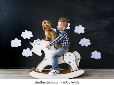 Cute baby boy riding wooden traditional rocking horse toy in room. The boy and yorkshire terrier. The boy and pet. Child playing in nursery room.
