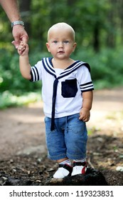 Cute baby boy in sailor outfit is holding parent's hand walking in forest