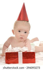 Cute baby boy sitting  with gifts on a white background