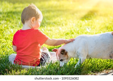 Cute Baby Boy Sitting In Grass Petting Dog.