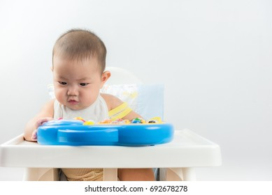 Cute Baby Boy Sitting In High Chair And Playing With His Toy