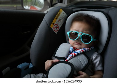 cute baby boy sitting on car seat safety belt lock protection for drive road trip travel in summer day