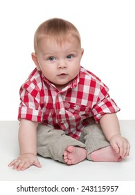 A cute baby boy is sitting on the white background