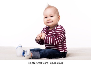 cute baby boy sitting on a blanket and smiling. child about eight - ten month looks at the camera