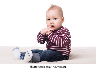 cute baby boy sitting on a blanket and looking at camera. child on a white background. happy family concept