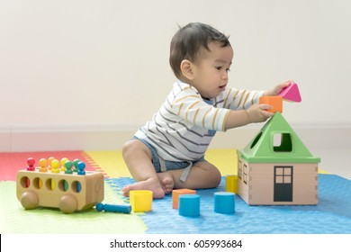 Cute baby boy sitting on a playmat and playing with toy by himself. Adorable eight month old child happy reach the toy.