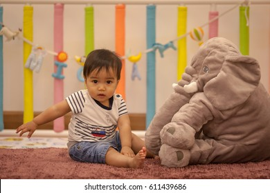 Cute baby boy sitting on a playmate and playing with toy by himself. Adorable eight month old child happy reach the toy,with blurred and select focus