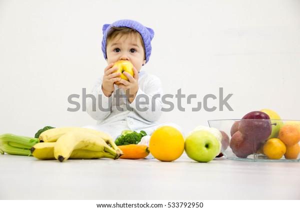 Un niño lindo sentado en la mesa con frutas y verduras y comiendo una manzana aislada de fondo blanco