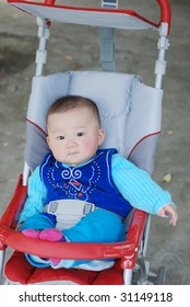 cute baby boy sitting in red baby carriage