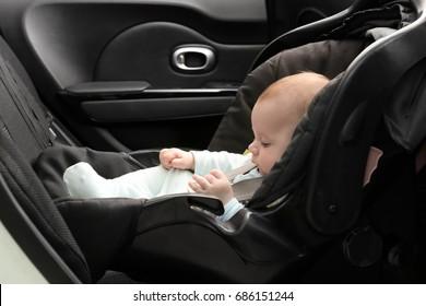Cute baby boy sitting in safety car seat